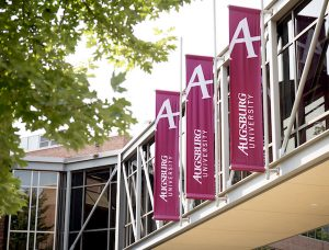Augsburg University banners hang from a skyway on campus