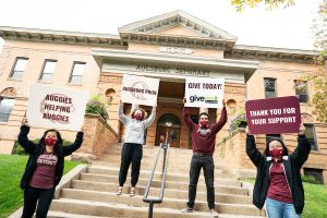 """Four Augsburg Students holding signs that read """"Auggies helping Auggies"""", """"Ausgburg Pride"""", """"Give Today"""" and """"Thank You for Your Support"""""""