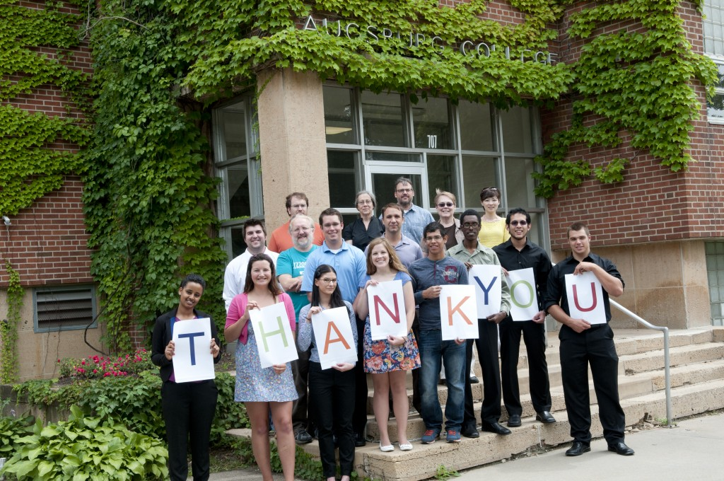 """Group of Auggies stands in front of Old Science, those in front hold signs which together spell """"thank you"""""""