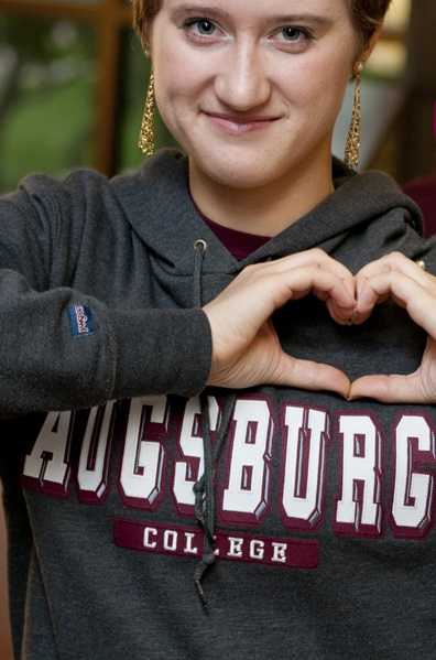 Person wearing Augsburg sweatshirt makes the shape of a heart with their hands