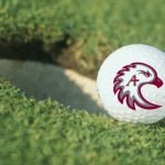 golf ball with Auggie Eagle logo next to a hole