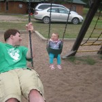 Brad Motl on swings with his infant daugter