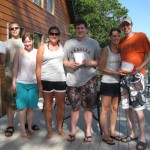 Six people posing with folded, frozen t-shirts