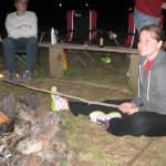 Kara Zetzman holds a marshmallow on a stick over a fire