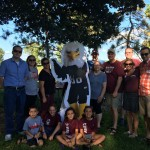 Augsburg Alumni gather around Auggie Eagle standup in a park in Rochester