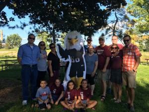 Augsburg Alumni gather around Auggie Eagle standup in a park in Rochester