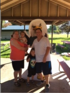 Family poses in front of Auggie Eagle standup