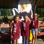 Three children wear Augsburg t-shirts in front of Auggie Eagle standup