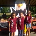 Three children wear Augsburg t-shirts in front of Auggie Eagle standup