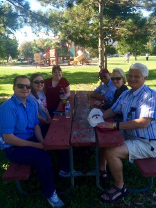 Augsburg alumni sit at a picnic table with Katie (Koch) Code