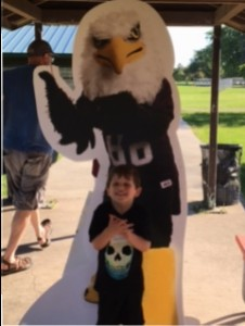 Child poses in front of Auggie Eagle standup