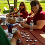 Katie Radford and Katie (Koch) Code sit at a picnic table with Augsburg buttons and other swag