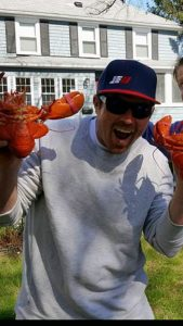 Jason Kusiak looking excited while holding two bright red lobsters.