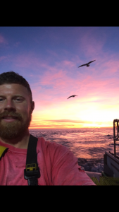 Jason Kusiak smiles for a selfie in front of a sunset over the ocean. Two birds soar overhead.