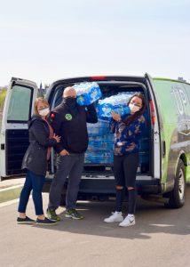 Bethany loading water bottles into van