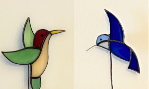 Two stained glass hummingbirds. On the left is a yellow, green, and red figure. On the right is a navy blue bird with a light blue head. Both come with planters