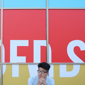 student in front of graphic design display