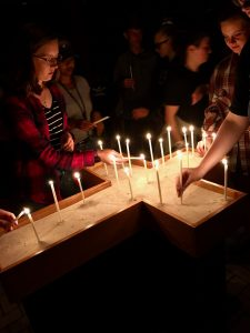 Students light candles in a cross formation