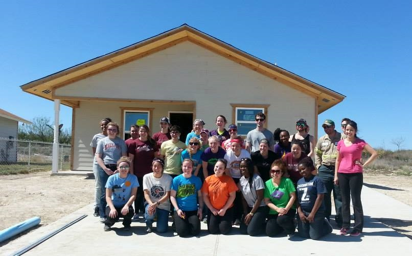 Group of Augsburg students with a Habitat for Humanity Homeowner in 2014.