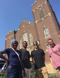 4 people standing in front of a church building