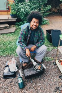 Tre smiling and tending a camp stove.