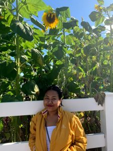Grace smiling in front of a white fence with tall sunflowers behind her