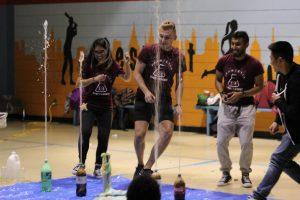 soda bottles spraying upward, students running away