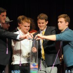 Students pour colored sand into glass cylinder at StepUP graduation