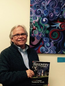 Photo of Scott W. holding a Recovery Campus magazine.
