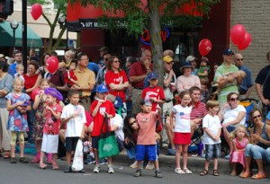 Children and adults, roadside, wearing red, white, and blue.