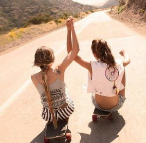 Two friends holding hands on a dirt road.