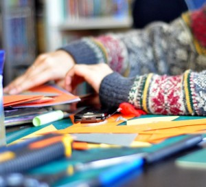 A person in a sweater working on crafts.