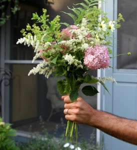 A hand holding a bouquet of flowers.