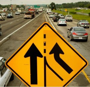 A merging sign in traffic.