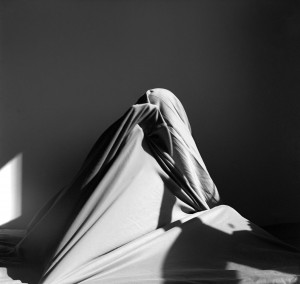 Black and white photo of a person tangled in sheets on a bed.