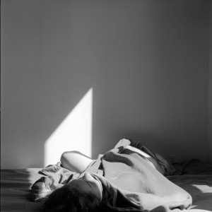 Black and white photo of a person laying in sheets on a bed.