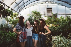 Four girls laughing in a green house.
