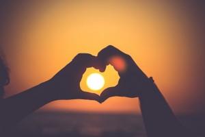 Hands making a heart surrounding the sun.