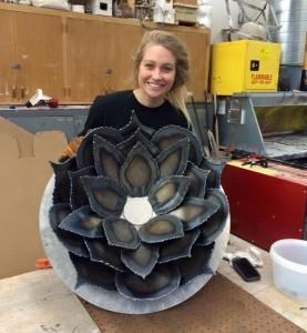 Lindsay holding up a welded metal flower.