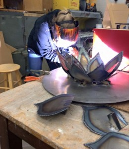 Lindsay welding pieces of a metal flower.