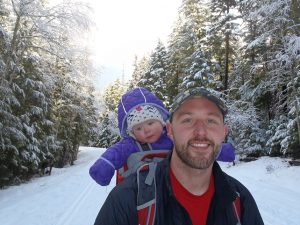 Shane J. with his daughter on a snowy trail in the woods.