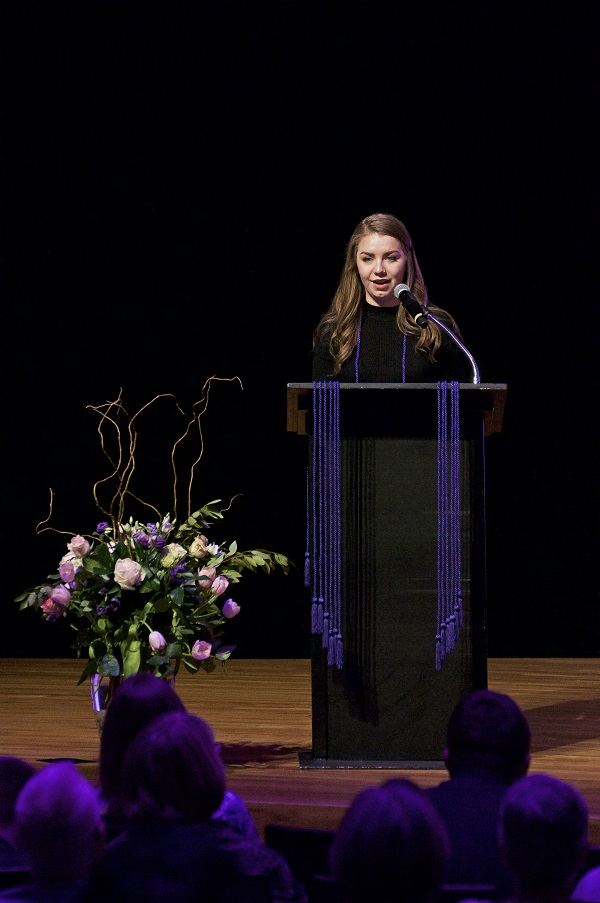Photo of Audrey C. Speaking at the Podium