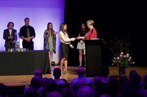 Photo of Sarah M. receiving her medallion form Kristin Wilcox
