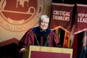 President Paul Pribbenow stands at a podium wearing academic regalia