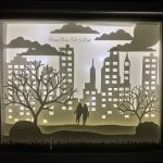Artwork by Jessica Hotchkiss. Shadow box. two people in the middle of a city scene.