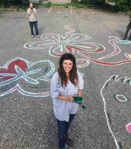 Greta McLain stands in a parking lot among large drawings of flowers on the concrete