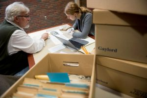 Phil Adamo studies at a table with a student. They are surrounded by boxes of files and papers.