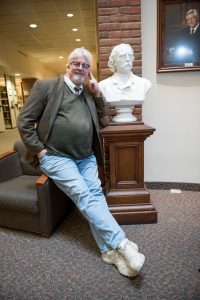 Phil Adamo perches on the arm of a chair, resting his elbow on a plinth displaying a bust in the Lindell Library