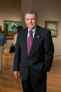 Joe (Orville C.) Hogander Jr. wears a suit and stands in an art gallery