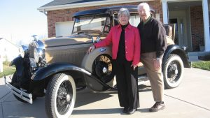 The Egertsons stand in their driveway with their collector car